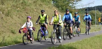 Grupa rowerzystów z dzieckiem na czele na asfaltowej ścieżce rowerowej